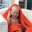 Adorable happy baby boy in orange towel — Stock Photo #21264147