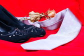 Black female shoes, rose and necktie on red background — Stock Photo
