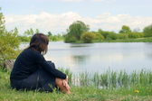 A woman sits alone and looks out across the river. — Stock Photo