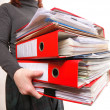 Female office worker carrying a stack of files — Stock Photo #22244675