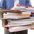 Male office worker carrying a stack of files — Stockfoto