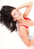 Latin woman in red lying on the floor white — Stock Photo