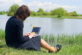 Woman typing on a laptop outside in a meadow — Stock Photo