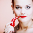 Beautiful woman with red lips and chilli pepper - Stock Photo