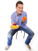 Young man with fruits full length isolated — Stock Photo