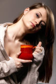 Pretty woman daydreaming while holding a tee cup — Stock Photo