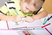 Jeune garçon mignon dessine avec des crayons de couleur — Photo