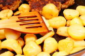 Seasoned potato slices in skillet pan in kitchen — Stock Photo