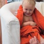 Adorable happy baby boy in orange towel — Stock Photo #22484823
