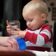 Baby boy playing with bottle and mug indoor — Stock Photo #22814802