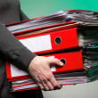 Stock Photo: Female office worker carrying a stack of files