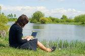 Frau eingabe auf einem laptop draußen auf einer wiese — Stockfoto