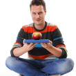 Man holding a book and one red apple full body - Stock Photo