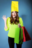 Surprised girl paper shopping bag on head. Sales. — Stock Photo