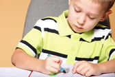 Young cute boy draws with color pencils — Stock Photo