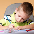 Young cute boy draws with color pencils — Stockfoto