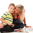 Mother playing puzzle together with her son — Stock Photo #23550365