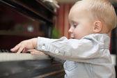 Pouco menino de tocar piano indoor — Foto Stock