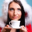 Beautiful girl santa claus Girl blowing hot drink — Stock Photo