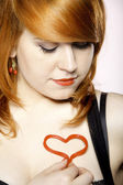 Happy redhair girl with heart love symbol on chest — Foto de Stock