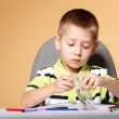Young cute boy draws with color pencils — Stock Photo #24074525