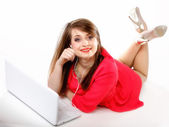 Cute girl with headphones and laptop lying — Stock Photo