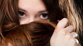 Tatlı kadın yüzü uzun kahverengi saçları tarafından kapsar — Stok fotoğraf
