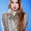 Portrait of young woman in fur blue background — Foto Stock