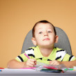 Young cute boy draws with color pencils — Stock Photo #24535083