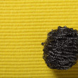 Yellow sponge background and steel scourer - Stock Photo