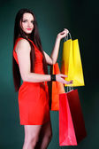 Young woman with paper multi coloured shopping bag — Stock Photo