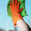 Gloved hand cleaning window with rag — Stock Photo