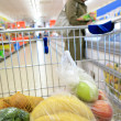 Shopping cart with grocery at supermarket — Stockfoto #24946283