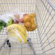 Shopping cart with grocery at supermarket — Stockfoto #24946285