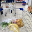 Shopping cart with grocery at supermarket — Stockfoto #24946463