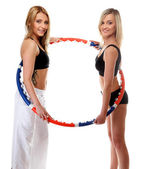 Two girls exercising with hula hoops in gym — Stock Photo