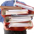 Stock Photo: Male office worker carrying stack of files