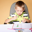 Young cute boy draws with color pencils — Stock Photo #25466561