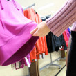 Shopping woman choose blouse at clothing shop — Stock fotografie