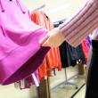 Shopping woman choose blouse at clothing shop — Stock Photo