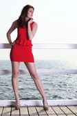 Young woman in red dress on the pier — Stock Photo