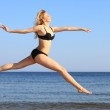 Young woman jumping on beach fit sporty girl — Stock Photo #25980059