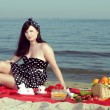 Picnic. Beautiful woman sitting on the blanket — Stock Photo #26061203