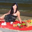 Picnic. Beautiful woman sitting on the blanket — Stock Photo #26061417