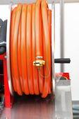 Rolled up of orange plastic hose — Stock Photo