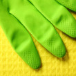 Yellow sponge and green rubber glove — Stock Photo