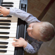 Little boy playing piano indoor — Stock Photo