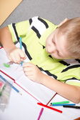 Young cute boy draws with color pencils — Photo