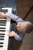Kleine jungen spielen klavier innen — Stockfoto