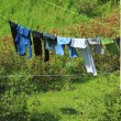 Clothes hanging to dry on a laundry line - Stock Photo